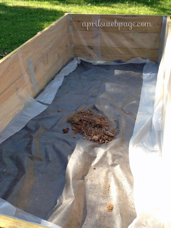 weed carpet and plastic lining in raised garden beds